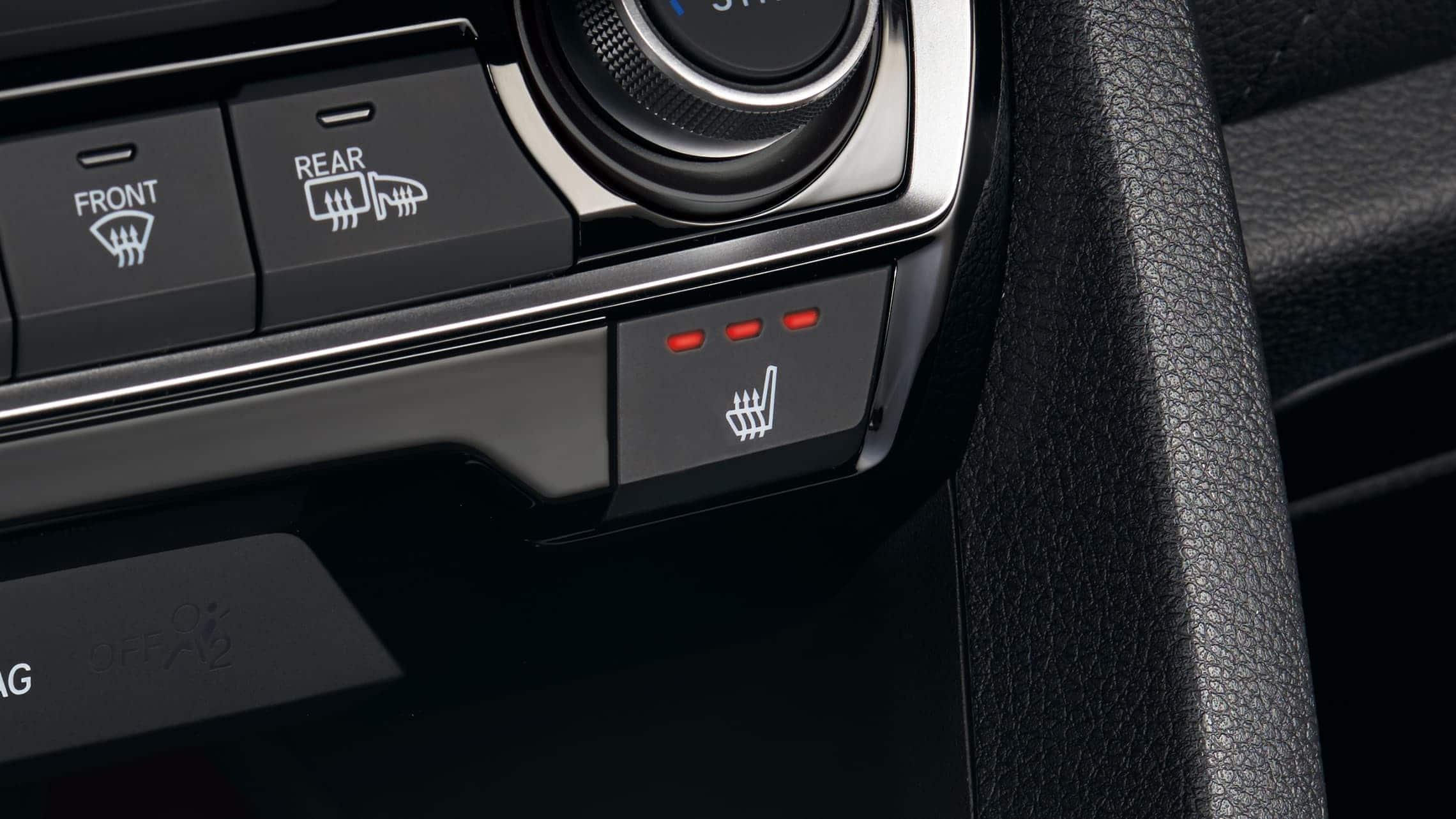 Detalle de los botones de los asientos delanteros calefaccionados en el Honda Civic Touring Sedán2020.
