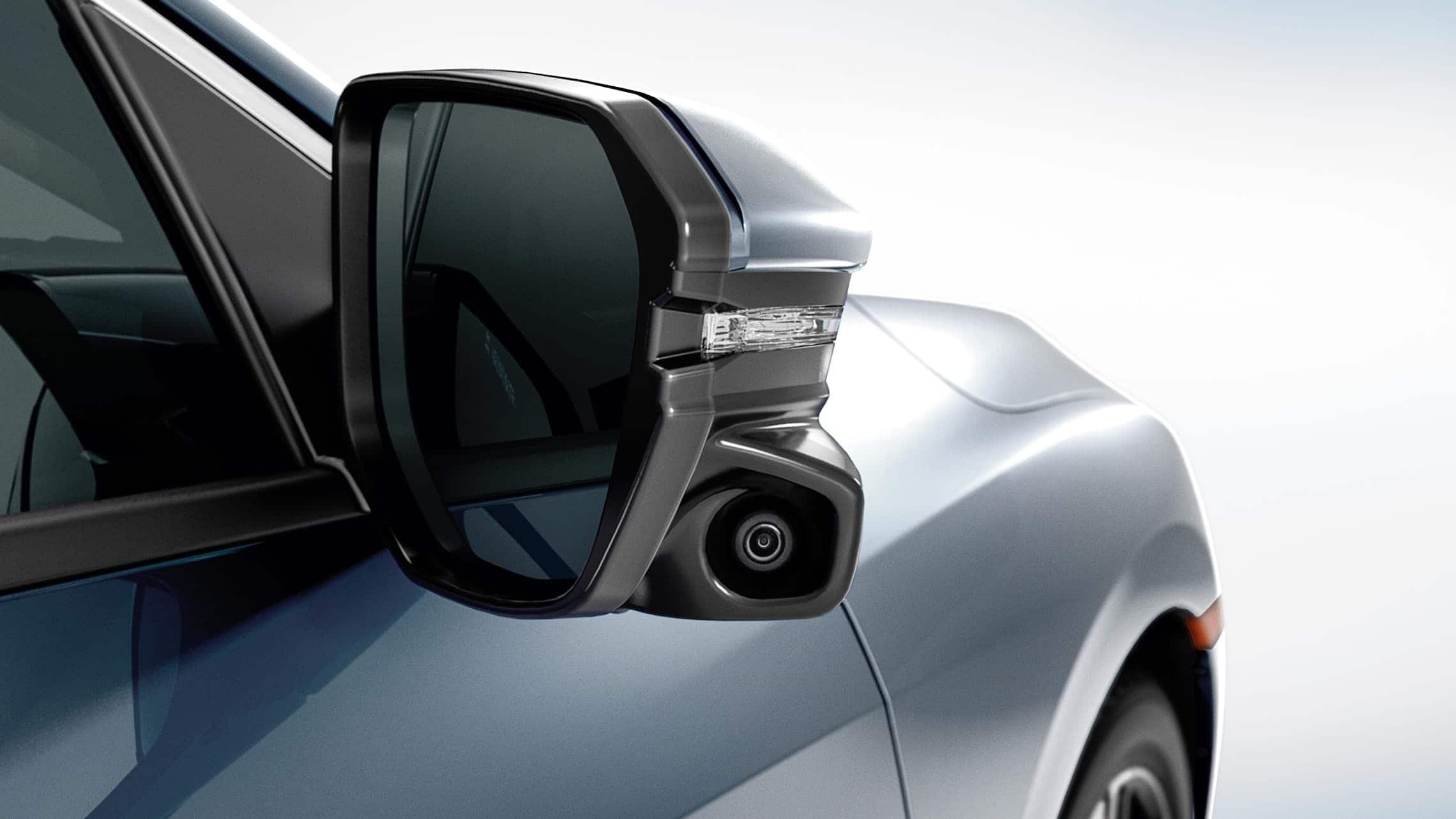 Detalle de la cámara Honda LaneWatch™ en el espejo del lado del pasajero del Honda Civic Touring Sedán2020 en Cosmic Blue Metallic.