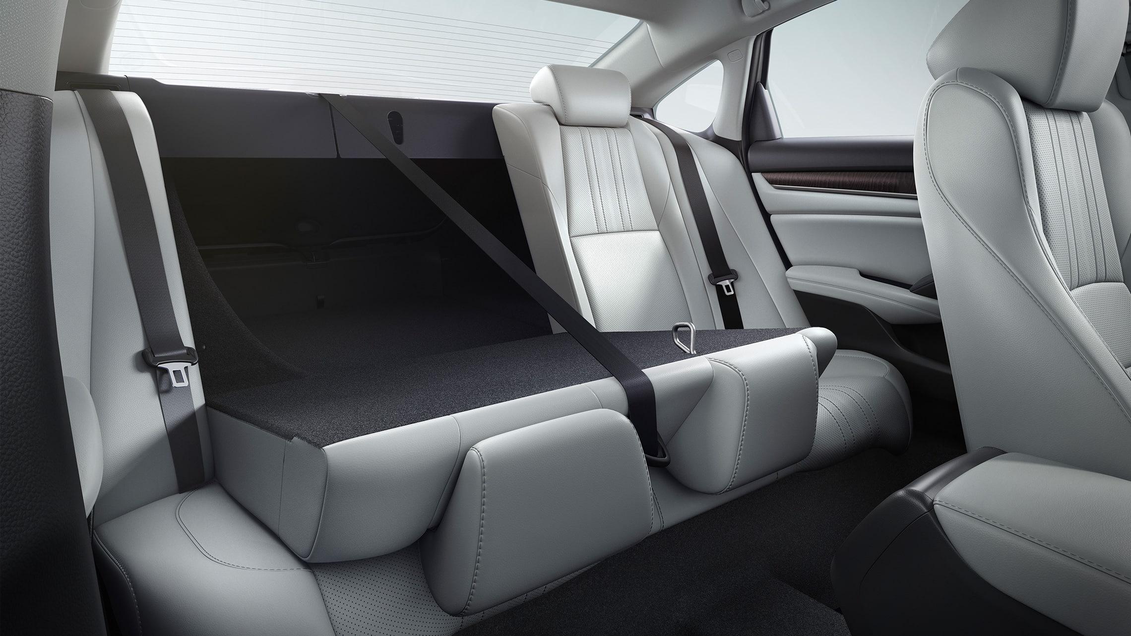 Detalle de los asientos traseros con respaldo abatible 60/40, que se muestran parcialmente abatidos, en el Honda Accord Touring2.0T2020 con Ivory Leather.