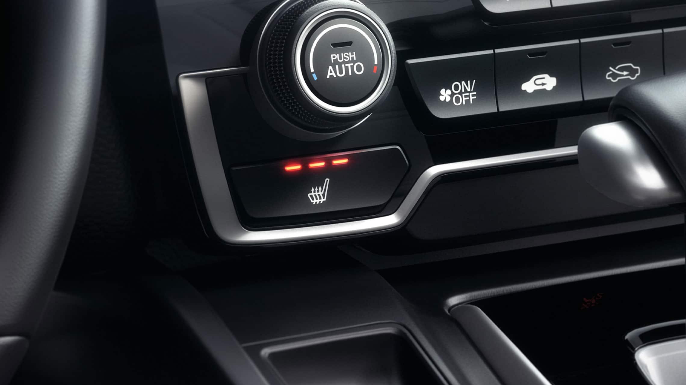 Detalle de los controles del asiento delantero con calefacción en el interior de la Honda CR-V 2020.