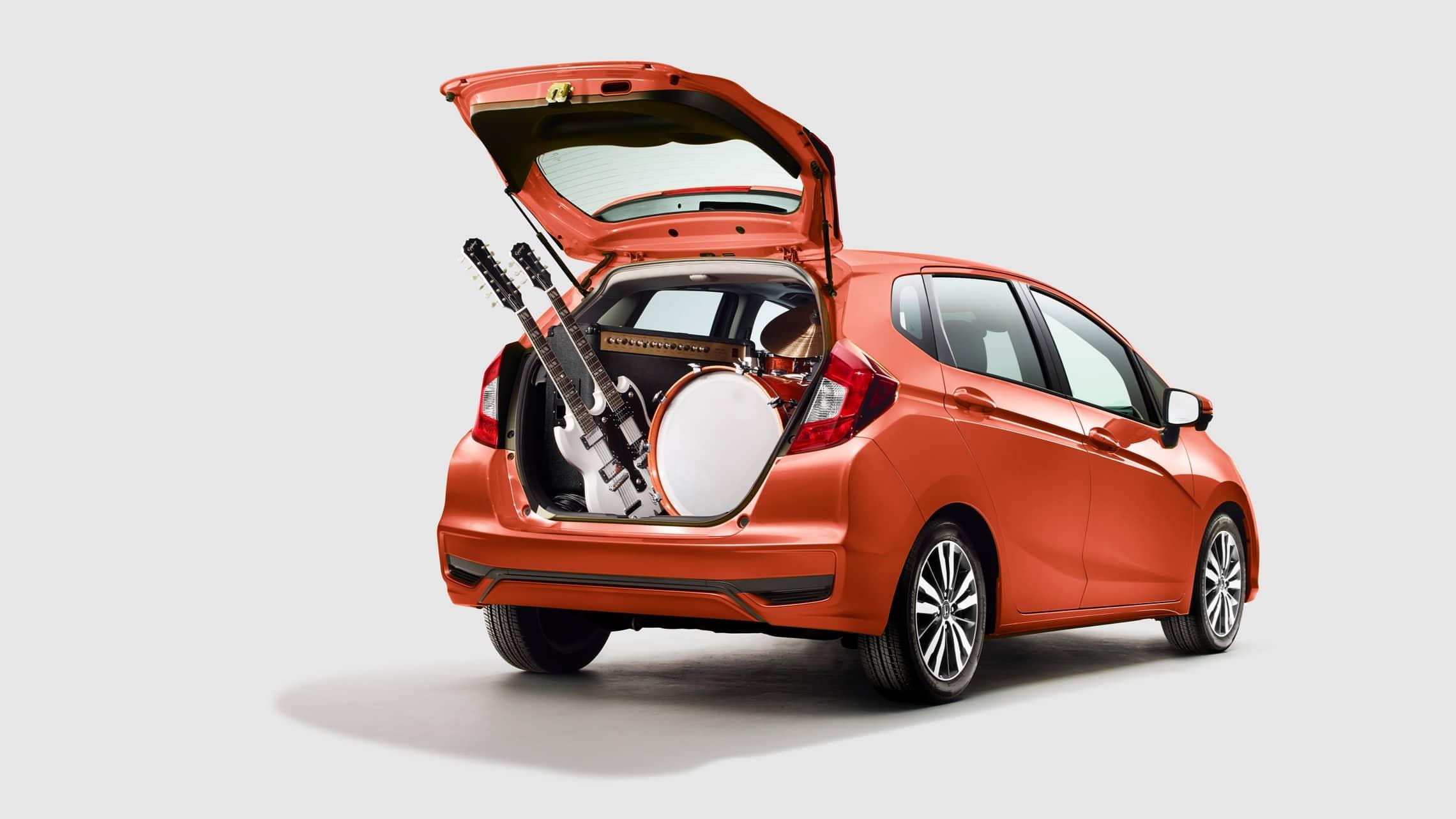 Vista trasera desde el lado del pasajero del Honda Fit EX-L2020 en Orange Fury con la puerta levadiza abierta e instrumentos musicales en el área de carga.