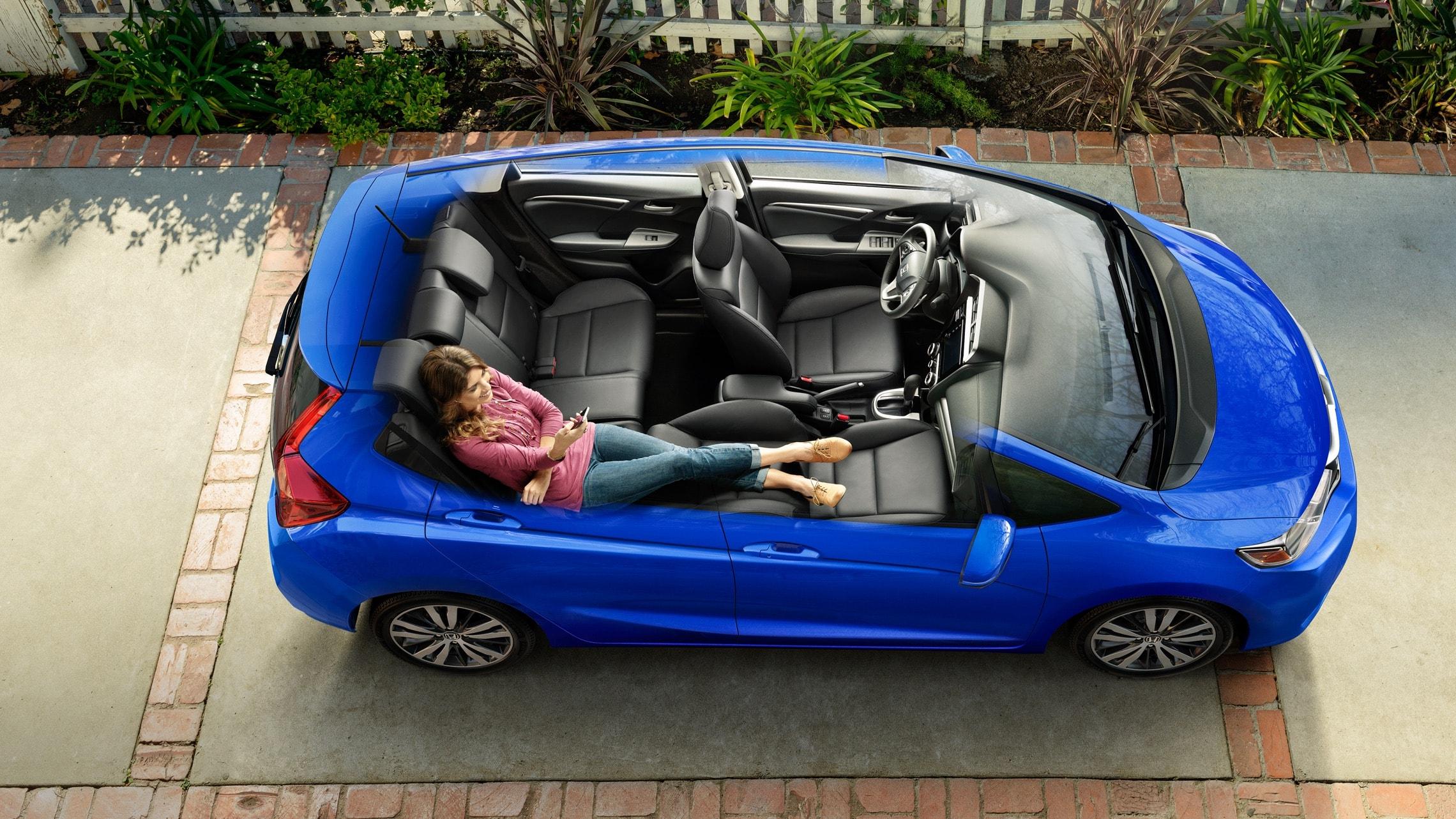 Vista interior aérea del Honda Fit EX-L2020 en Aegean Blue Metallic con el asiento del pasajero delantero reclinado por completo hacia atrás y los asientos Magic Seat® en la segunda fila reclinados.