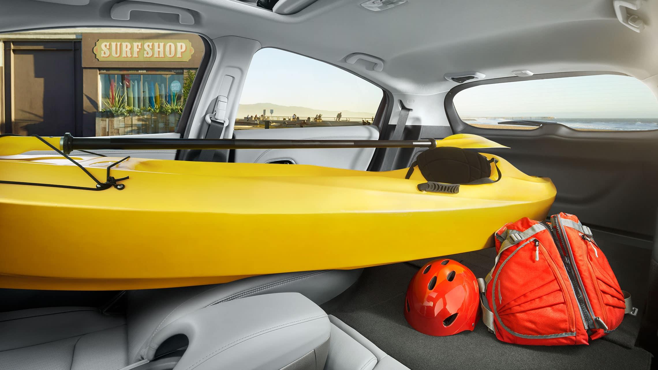 Vista interior de la Honda HR-V Touring2020 con Gray Leather con todos los asientos traseros y el asiento del pasajero abatidos para llevar un kayak y equipaje.