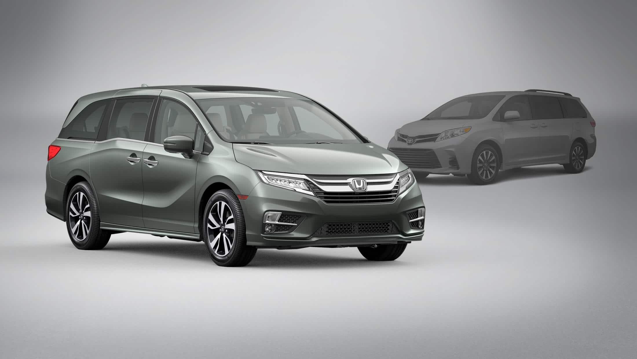 Vista frontal de 3/4 desde el lado del pasajero de la Honda Odyssey2020 en Forest Mist Metallic estacionada frente a una Toyota Sienna2020.